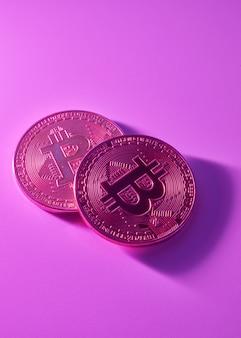 Две золотые биткойны, изолированные на розовом фиолетовом фоне крупным планом с копией пространства