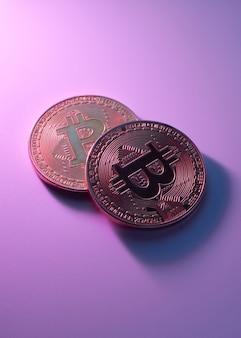 コピースペースとピンク紫の背景のクローズアップで分離された2つの黄金のビットコイン