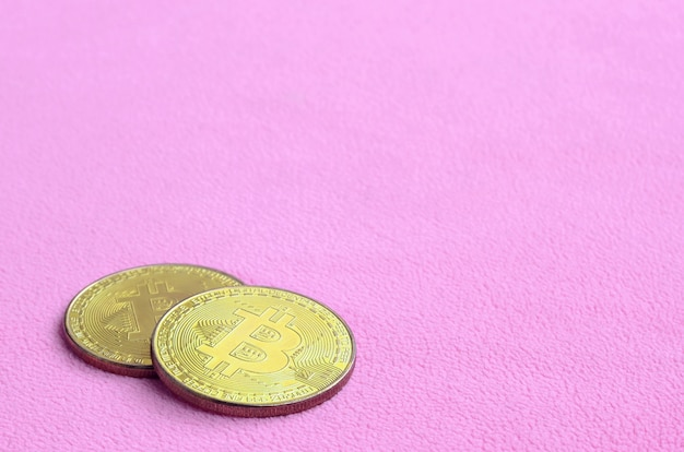 Two golden bitcoins lies on a blanket made of soft and fluffy light pink fleece fabric