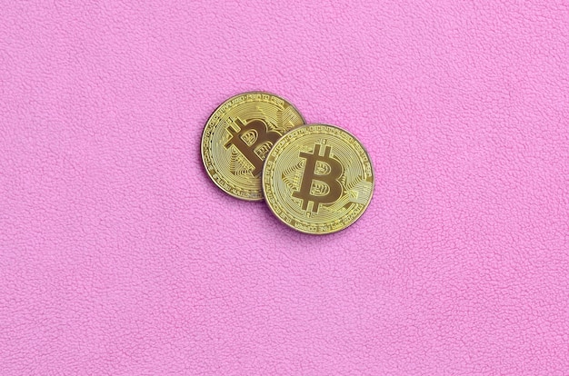 Two golden bitcoins lies on a blanket made of soft and fluffy