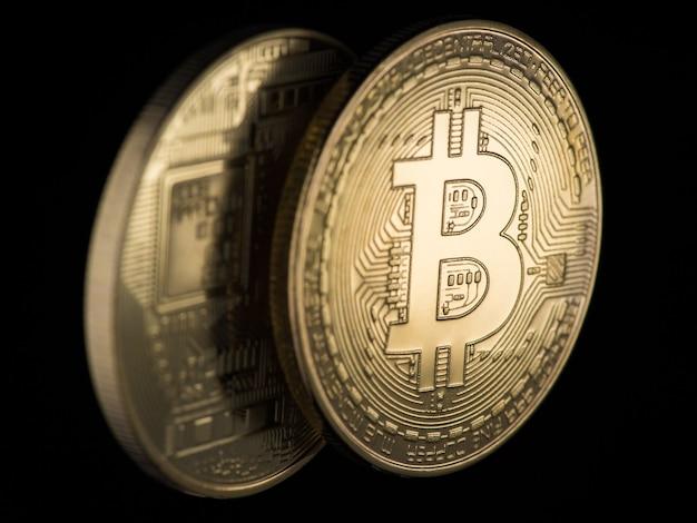 Две золотые биткойны на черном фоне, крупным планом. электронные деньги