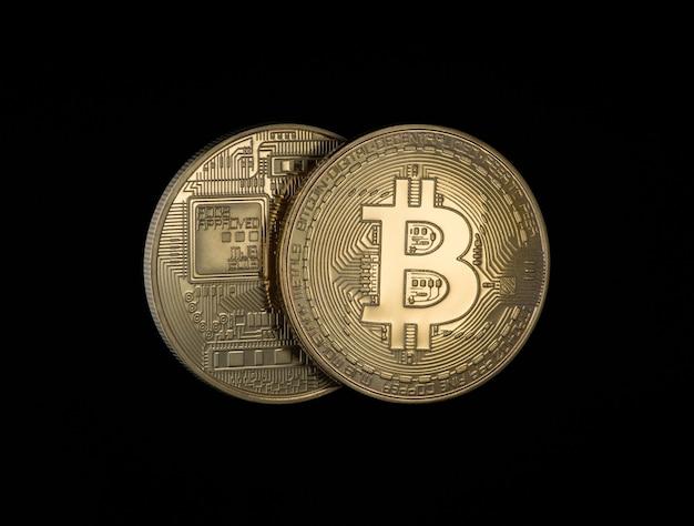 Две золотые биткойны на черном фоне. электронные деньги изолированные