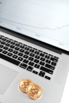 Two golden bitcoins placed on silver laptop with financial chart on its screen