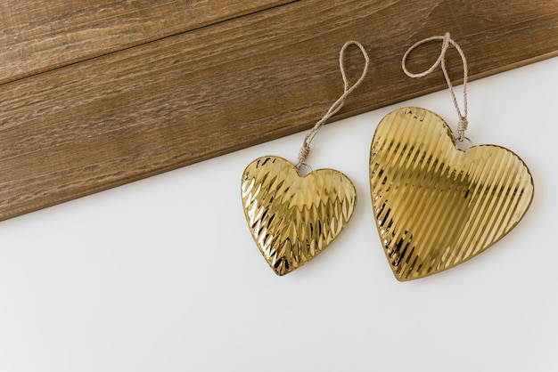 Two golden heart shape on white backdrop