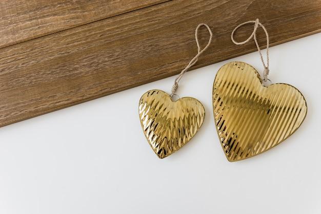 Two golden heart shape on white backdrop