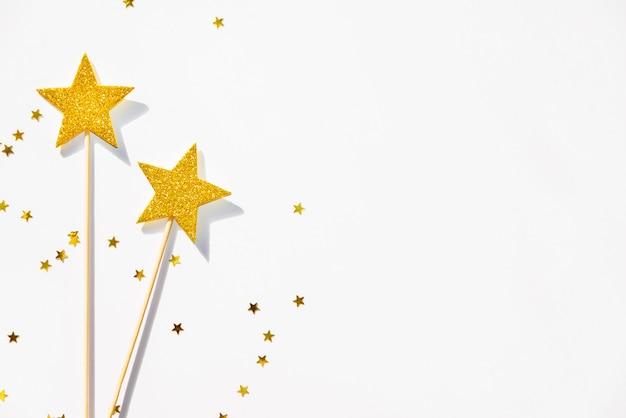 Две золотые партии волшебные палочки и блестки на белом фоне. копировать пространство