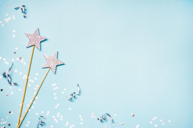 Две золотые партии волшебные палочки, блестки и ленты на белом фоне. копировать пространство