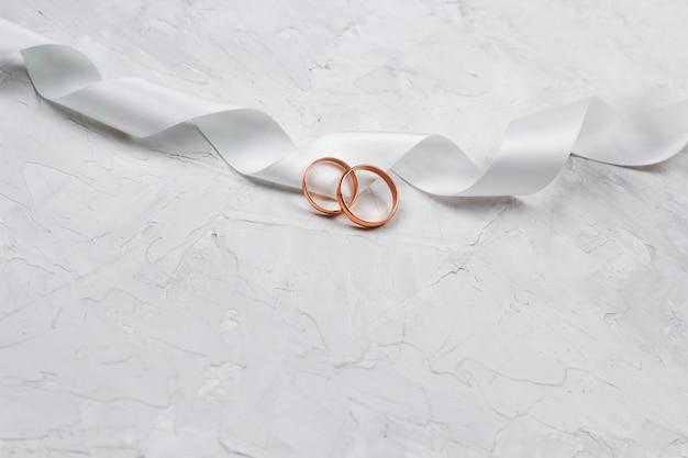 두 개의 황금 반지와 흰색 새틴 리본 결혼식 장식 또는 결혼식 초대 배경 개념