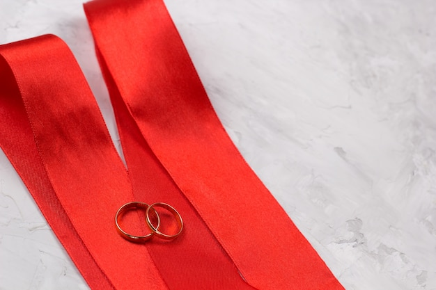 Two golden rings and red satin ribbon wedding decor or wedding invitation background concept