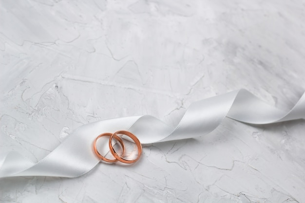 Two golden rings and white satin ribbon wedding decor or wedding invitation background concept