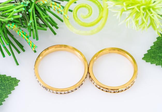 白い背景の上の2つの金色の結婚指輪と枝の花