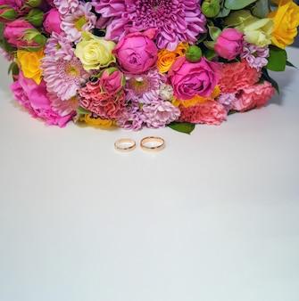 Два золотых обручальных кольца и красочные цветы на белом фоне свадебный фон копией пространства