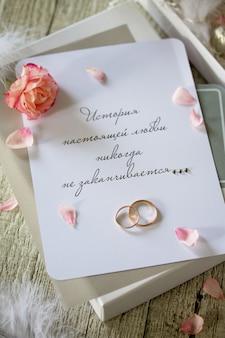 チョコレートの2つのゴールデン結婚指輪ボックスと結婚式の招待状