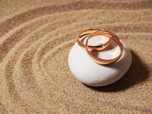 Два золотых обручальных кольца заделывают на серых камешках. свадьба на пляже концепции приглашения карты.