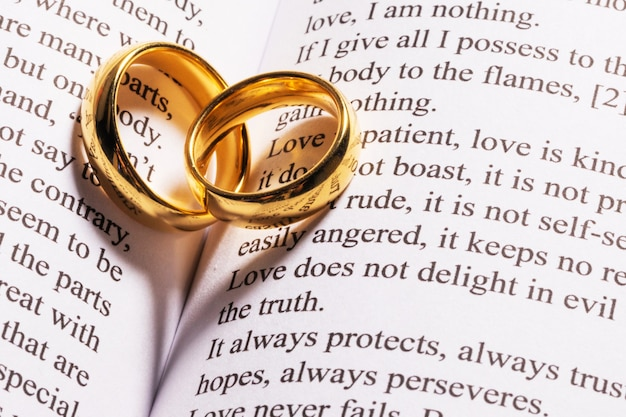 Two golden wedding rings on holy bible book close up