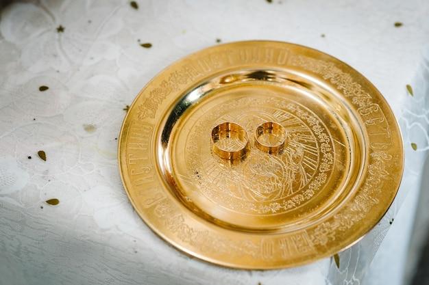 Два золотых обручальных кольца в тарелке на столе на церемонии перед венчанием в церкви.