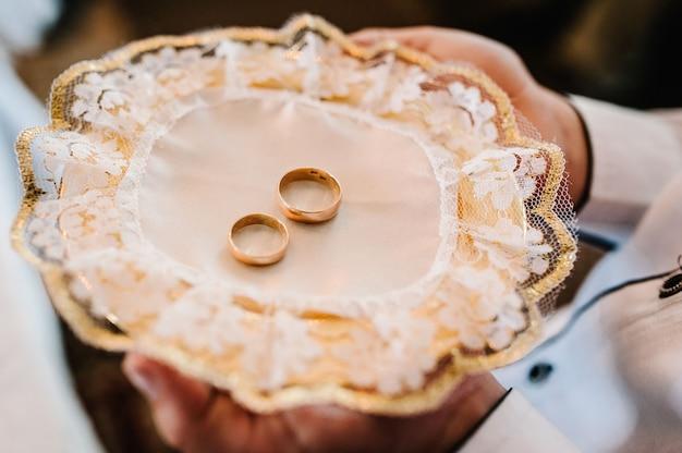 Два золотых обручальных кольца в тарелке на столе на церемонии.
