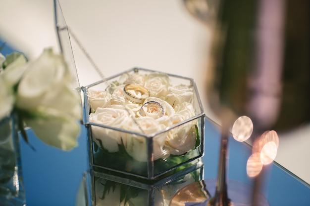 Два золотых обручальных кольца в стеклянной коробке