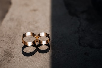 Two golden wedding rings lie in the ray of light