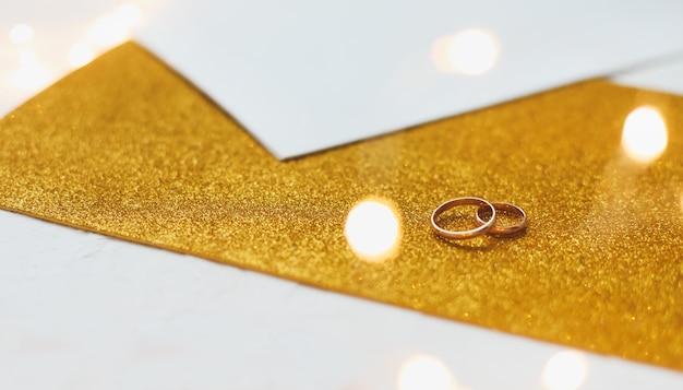 金色の背景に2つの金色の結婚指輪。
