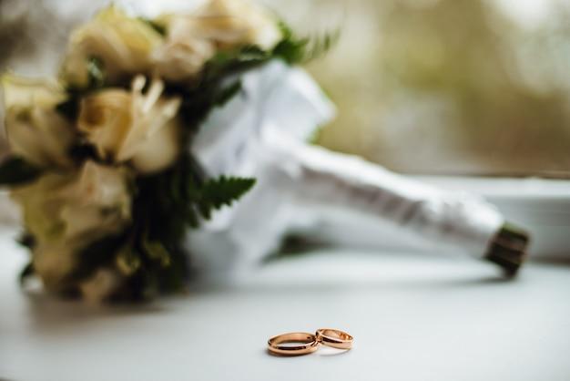 꽃다발 두 황금 결혼 반지