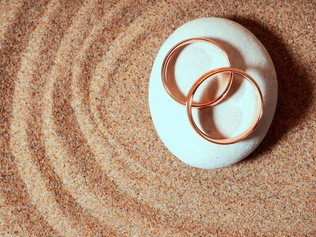 Два золотых свадебных солнышка лежат на камнях в форме дзен, медового месяца.