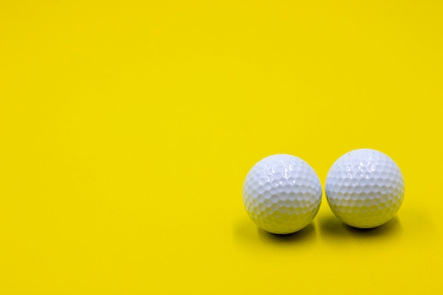 Two golf balls are on yellow background