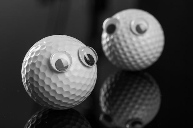 Два мяча для гольфа с глазами на серой поверхности