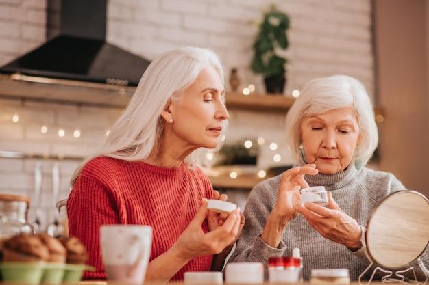 새로운 크림을 바르는 두 명의 잘 생긴 노인 여성