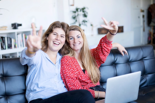 Two gorgeous brunette woman   with smile and showing peace sign with fingers
