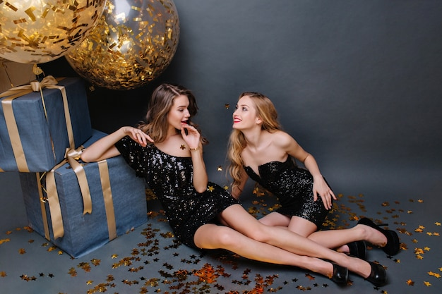 Two gorgeous fashionable young women in luxury black dresses sitting on floor. having fun, elegant look, long curly hair. big present, golden balloons, tinsels.