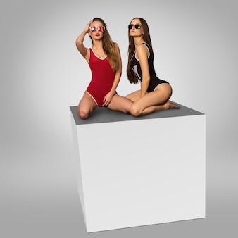 2人のゴージャスな女の子が灰色の背景にスタジオの立方体に座っています