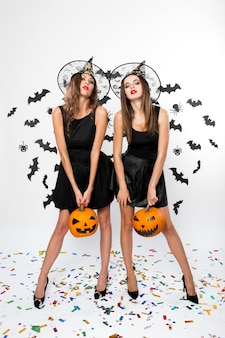 黒のドレス、魔女の帽子、ハイヒールを身に着けている2人のゴージャスな女の子は、バットで背景にハロウィーンのカボチャを保持します。