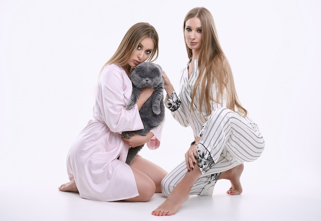 Two gorgeous model girls in a pajamas posing with a fat pedigree cat