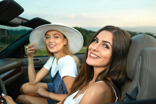 Two gorgeous models posing in cabriolet and smiling.