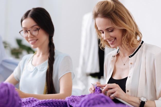 보라색 실로 뜨개질을 하고이 여가 시간 동안 자신을 즐기는 것처럼 보이는 두 명의 멋진 즐거운 여성