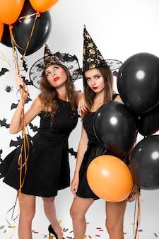검은 드레스와 마녀 모자를 쓴 두 명의 멋진 여성이 검은색과 주황색 풍선을 들고 있습니다. 할로윈 .