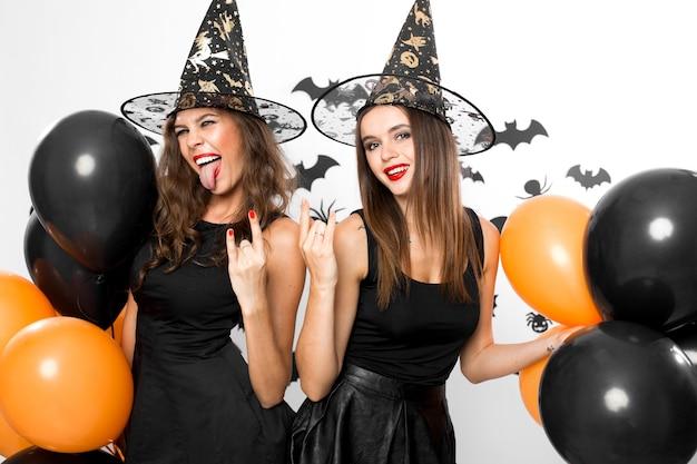 검은 드레스와 마녀 모자를 쓴 두 명의 멋진 여성이 찡그린 얼굴을 하고 검은색과 주황색 풍선을 들고 있습니다. 할로윈 .