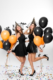 검은 드레스, 마녀 모자, 하이힐을 입은 두 명의 멋진 여성이 검은색과 주황색 풍선을 들고 있습니다. 할로윈 파티 .