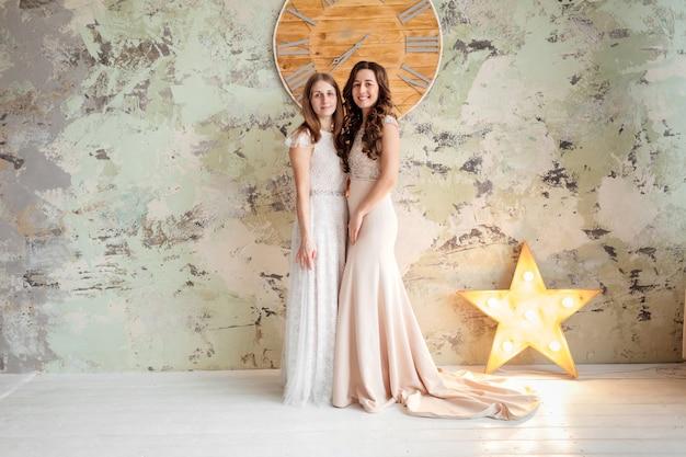 Две великолепные молодые женщины, одетые в изысканные длинные платья с кружевным верхом на фоне кирпичной стены с большими часами и звездой.
