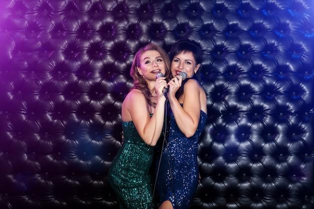 Две великолепные молодые женщины в праздничных платьях поют караоке