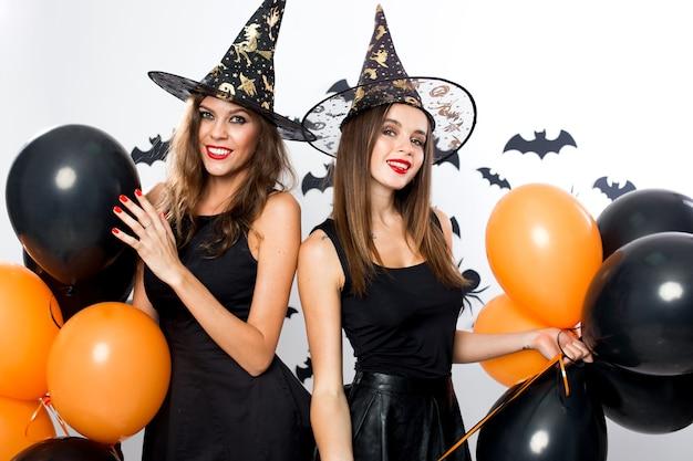 검은 드레스와 마녀 모자를 쓴 두 명의 화려한 여성이 검은색과 주황색 풍선을 들고 있습니다. 할로윈 .