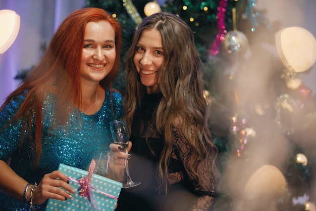Two graceful women rejoices with a gift box near a christmas tree. women laughs, smiles, poses. special vintage noise and grain filter, blurry lights.