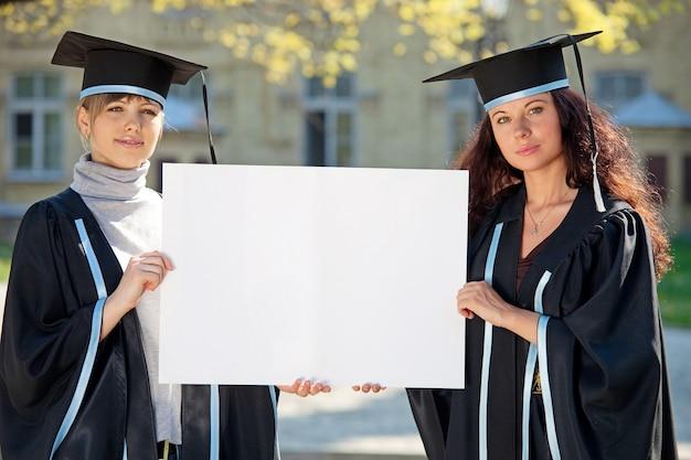 Два выпускника держат чистый лист