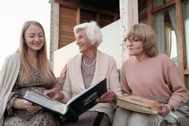 Two grandmothers showing their family album to their granddaughter while they sitting outdoors