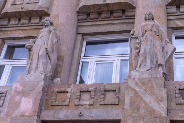 현대적인 창문을 배경으로 부다페스트 빌딩 벽에 냄비와 칼이 있는 2개의 화강암 여성 동상