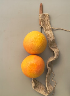 背景に編み物の横に置かれた2つのグレープフルーツ