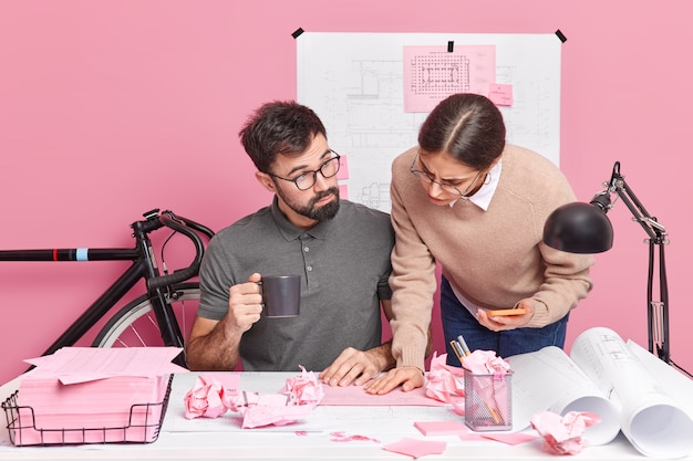 Two graphic designers collaborate on building sketches share different ideas for creating new room brainstorm together pose at desktop