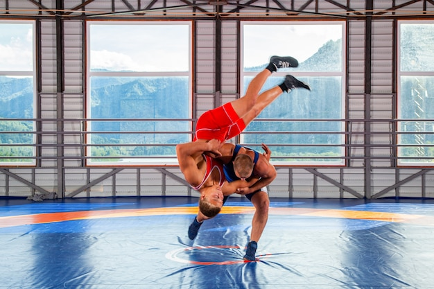 Two greco-roman wrestlers in red and blue uniform making a thigh throw on a wrestling carpet in the gym.