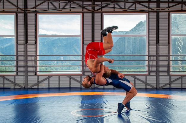 Two greco-roman wrestlers in red and blue uniform wrestling on a wrestling carpet in the gym.